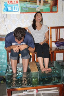 """This is a parlor where """"kissing fish"""" can eat the dead skin off your feet. I saw it and couldn't resist giving it a try. It tickled like hell, but I made it happened... Donna was more hesitant but eventually fully submerged her feet as well."""