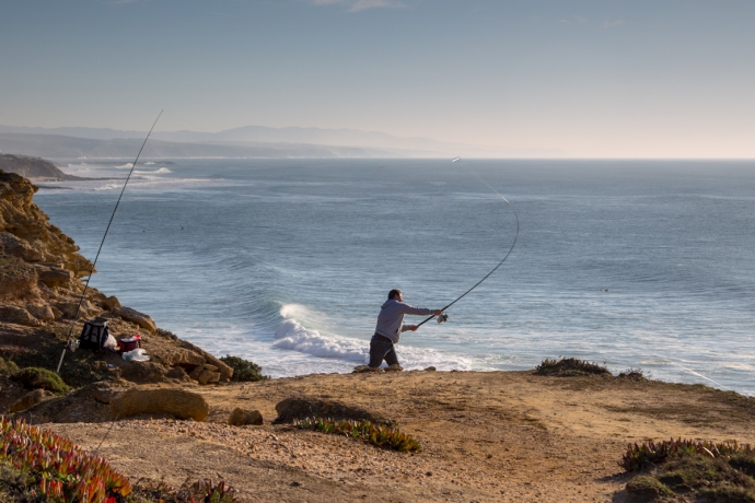 Fisherman casting from atop the cliffs above Ribeira d'Ilhas .  He would send his bait flying about 100 yards into the ocean below!